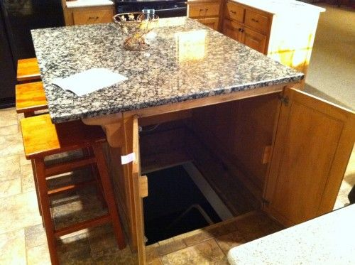The door to an underground storm shelter or panic room in the kitchen island! Best secret passage ever.  Definitely a dream home feature! Or secret hide out!