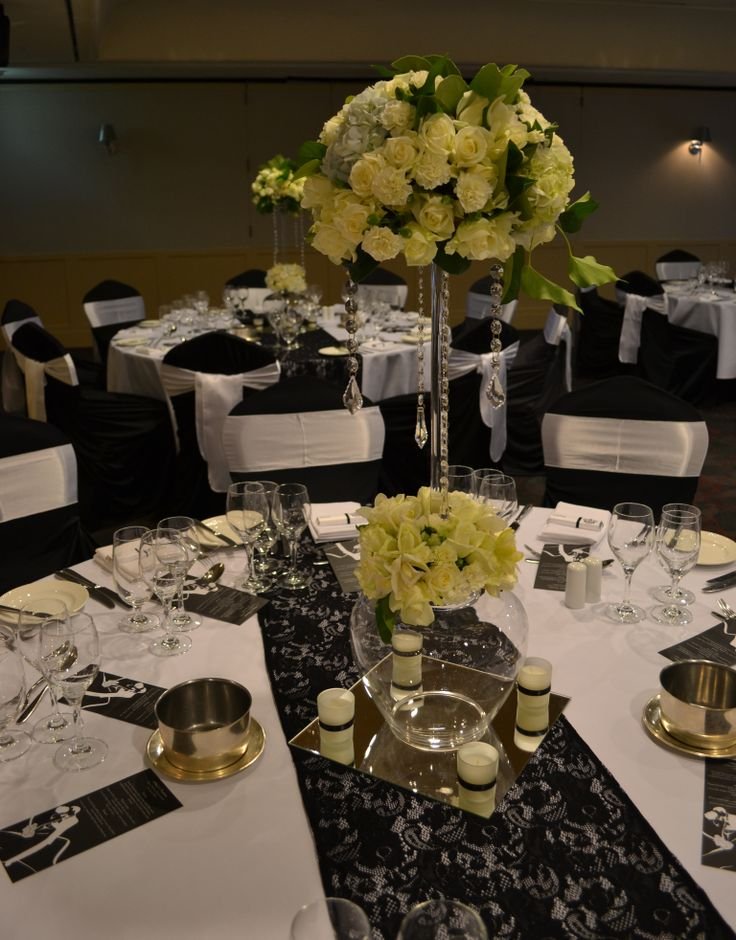 Black and white wedding reception. Black lace runners and tall white floral arrangements. Styled by Greenstone Events.
