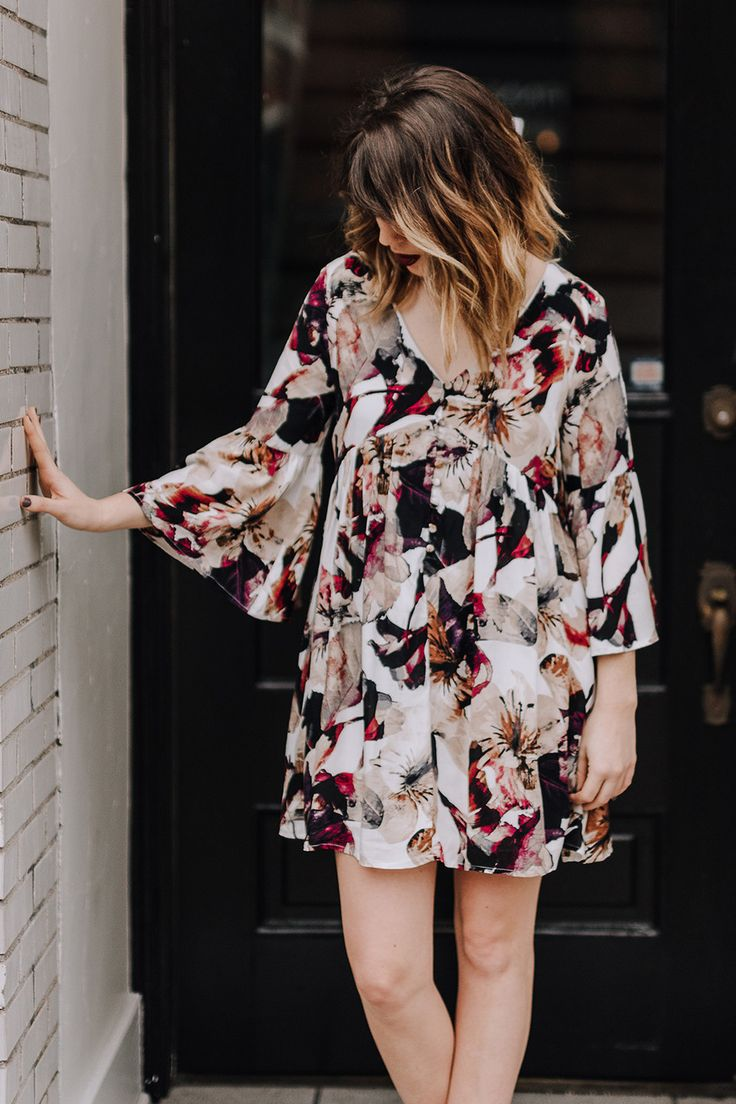 Floral print baby doll button down dress featuring 3/4 bell sleeve and loose baby doll fit. The front has a v-neckline with a quarter button down detail. Fully-lined. Model is wearing a S.
