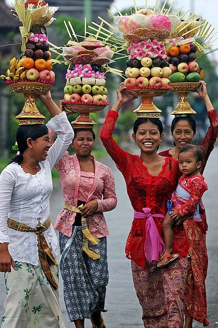 A group of traditional balinesse woman lifted the bundle of fruits in their head up (indeed one of them brings a child also). It called 'sesajen' to celebrate one of hinduism traditional ritual in Bali, Indonesia