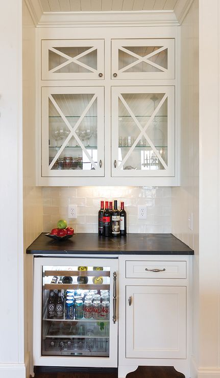 Butler pantry nook is filled with glass front upper cabinets and ivory lower cabinets fitted with a glass front beverage fridge paired with a soapstone countertop and a white glazed subway tile backsplash.