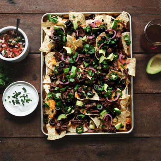 Beer braised steak nachos with pickled onions and pico de gallo.