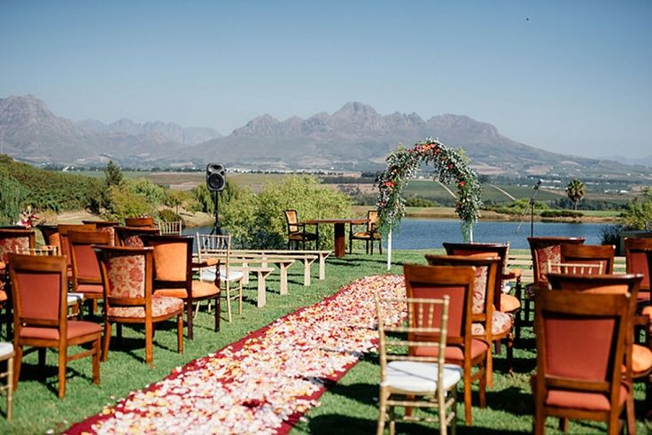 Floral arch, eclectic chairs, mountain view