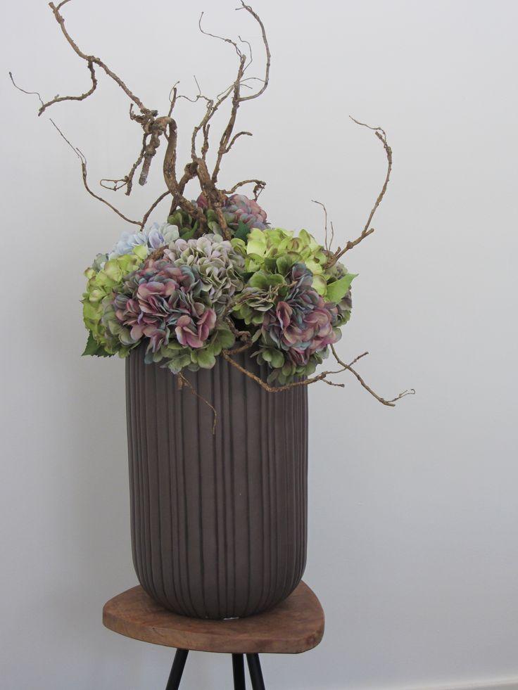 Hoge bruine ribbel pot gevuld met een mix van kunst hortensia's en afgewerkt met een speelse kronkeltak. www.Abonneefleur.nl