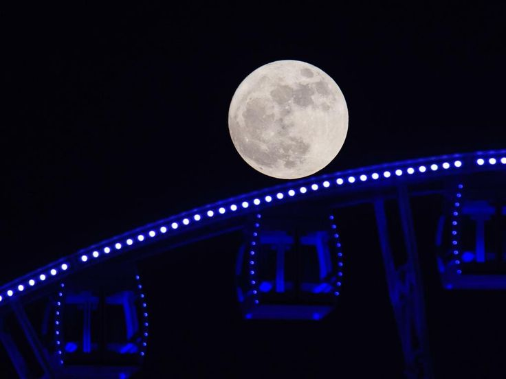 """A """"supermoon"""" is seen rising beyond a ferris wheel in Hong Kong on November 14, 2016. Picture: AFP PHOTO / ANTHONY WALLACE"""