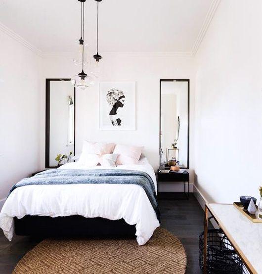Rose quartz pillowcases; white sheets; slate-blue blanket; sisal rug; black lights and mirror frames