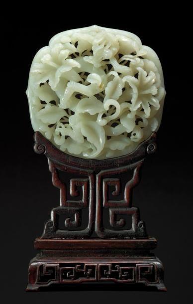 Belle et rare plaque en jade blanc ajouré représentant un phénix perché sur une branche d'arbre dont les fleurs et les feuillages sont traités en enroulement, la bordure en forme de lotus. Au revers l'encadrement sculpté de huit chimères opposées. Période Qianlong (1736-1795) L: 9cm. Posé sur un socle en bois ajouré postérieur