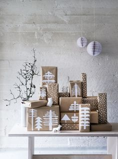 """Christmas presents are wrapped with brown kraft paper. Decorations are made from white paper cut into tree shapes. Glue the paper trees onto the package. White paint pens create the """"snowfall"""" design."""
