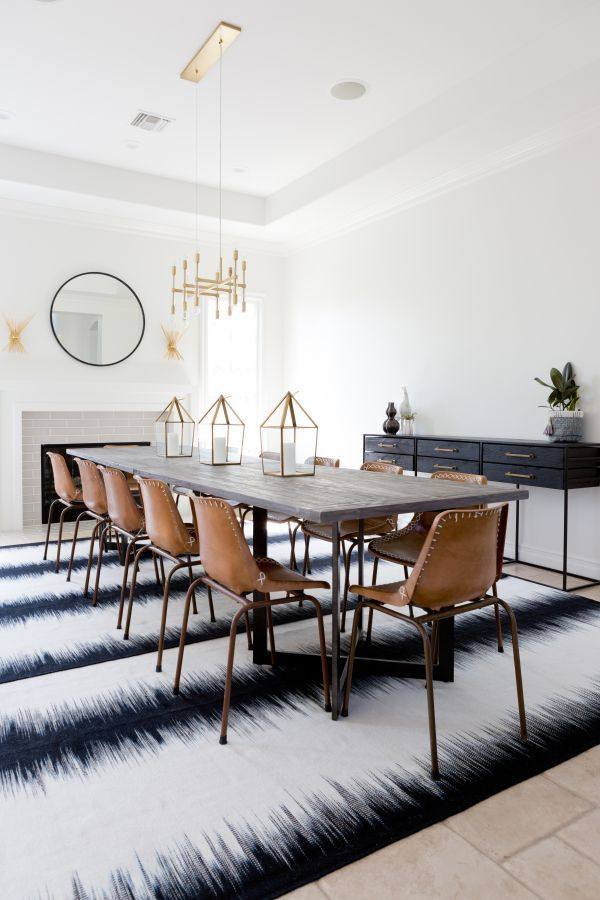 Extra long dining room table, leather school house chairs, and brass  chandelier.