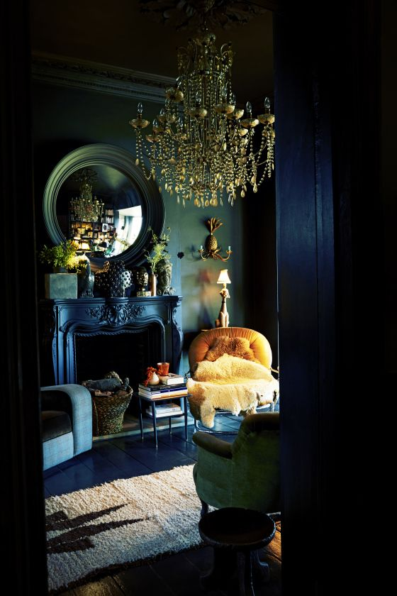 A buttercup yellow tufted chair becomes the focalpoint in this dark teal room with its antique black fireplace. Notice how the yellow compliments the golden chandelier. For the brave of heart!jj. Boho luxe. Bohemian glam.