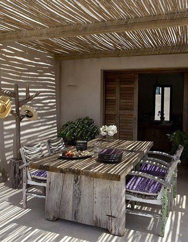 Pergola toit canisse de bambou montée sur structure poteaux bois pour protéger terrasse devant maison