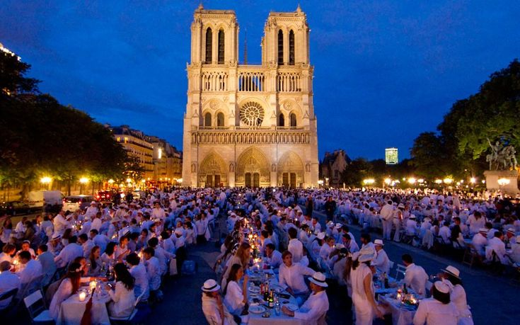 People attend the White Dinner event in front of the Notre Dame Cathedral in Paris