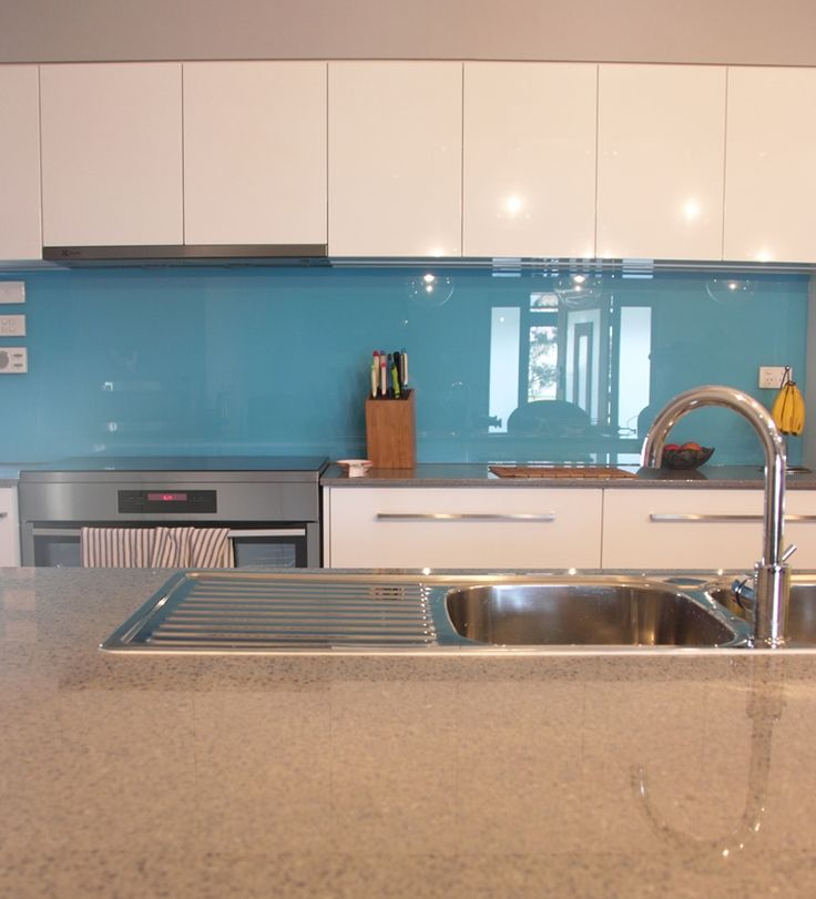 Silestone top in Galaxy and gloss white vinyl wrap doors, blue glass splashback