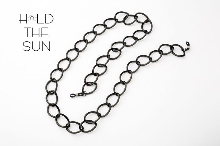 LOOPED IN • Sunglasses chain in black with wide loops. • Inspired by the stories that bond us together. • Attachments are adjustable to fit any size eyewear frame by sliding the metal spring up & down.