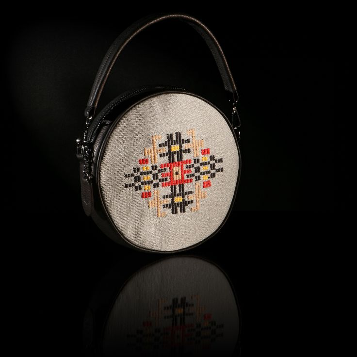 "The handmade woven round bag ""Iris"" adorns a pattern inspired of a traditional female outfit of Thrace. The color of the leather is black and the background is in grey silk weaving."