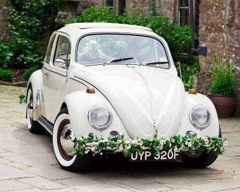 déco de voiture rétro pour mariage avec une guirlande verte et fleurs blanches délicates