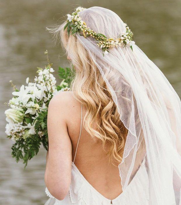 Coiffure mariage - Une couronne de fleurs avec un voile et des cheveux ondulés