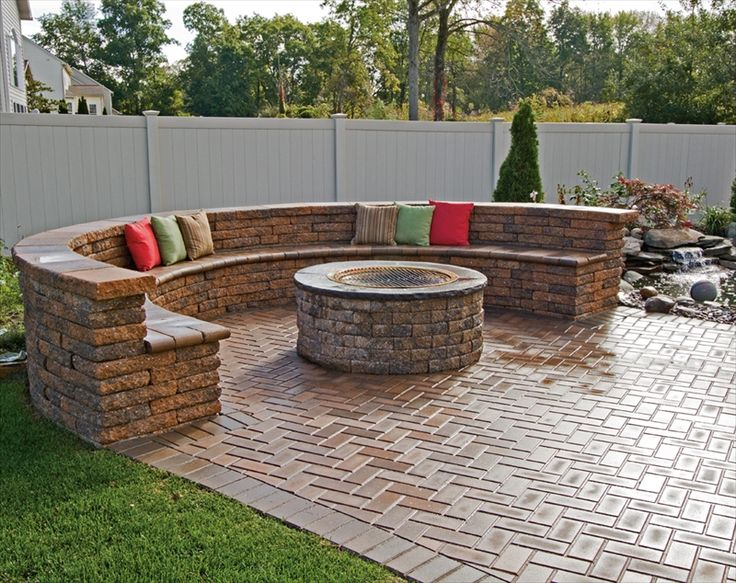 Love the feel of a built in sofa incorporated onto a patio with firepit.  Sitting there and listening to the sound of the water from the water feature next to it would be so relaxing.