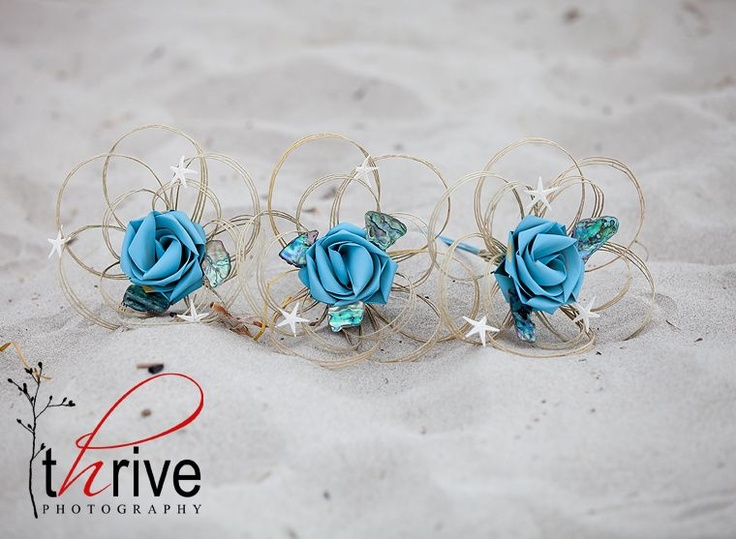 Single flower bouquets with paua pieces and tiny star fish.  www.flaxation.co.nz