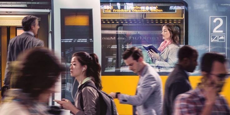 Una mujer lee la Biblia en un tren mientras las demás personas caminan deprisa por la estación