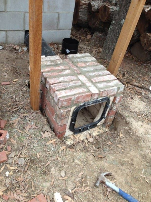 Nick then created a fire box from brick and connected it to the black smoke tube that leads into the smokehouse. He purchased and installed a door for the fire box to close when in use.