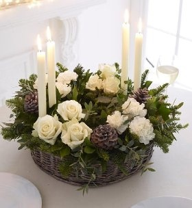 A wreath ring for an indulgent Christmas look, with white Kenyan roses and white carnations beautifully arranged with noble pine, berried ivy, frosted eucalyptus and glittered pinecones. 6 x Standard carnation white 6 x Rose white Kenyan 2 x Berried ivy 3 x Noble pine 2 x Eucalyptus parvi frosted 3 x Pine cones glittered Presented in a wicker oasis ring with 4 candles and holders Basket dimensions: H100 x D450mm