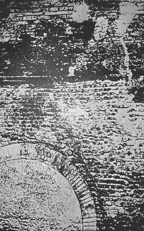 Baptistère St-Jean: Elévation sud, partie inférieure droite.- 87) BAPTISTERE ST-JEAN à POITIERS: Seule la photographie à la lumière artificielle nous a permis de prendre connaissance de cet ensemble, qu'il a fallu examiner à tâtons, l'espace entre la muraille qui fait face et la tranche de l'ouverture ne laissant pas passer la tête. Une air de béton gris romain lui sert de base et vers le S un blocage, comme les éléments précédents, a été coupé par l'établissement de la piscine.