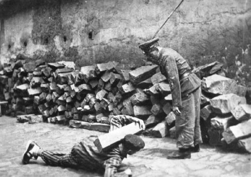 An SS guard photographed while beating a concentration camp prisoner.