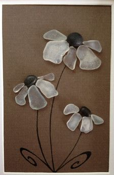 Genuine White Sea glass collected from a beach on the coast of California arranged into a collage of flowers with beach pebbles as centers with a brown background. Framed and matted in a 9 x 7 black frame.