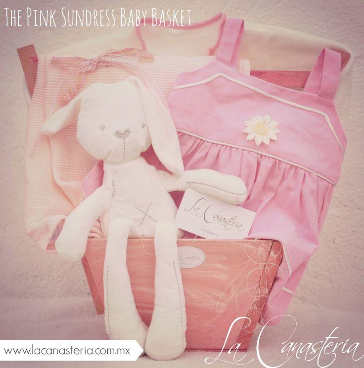 The Pink Sundress Baby Basket es una monada de regalo para bebita con un tierno vestido de verano con florecitas estilo girasol, sweter coordinado, nuestro conejo ultra suave de importación y más! …