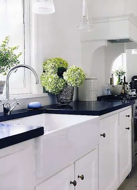 Black concrete countertops with white units and walls with the belfast sink