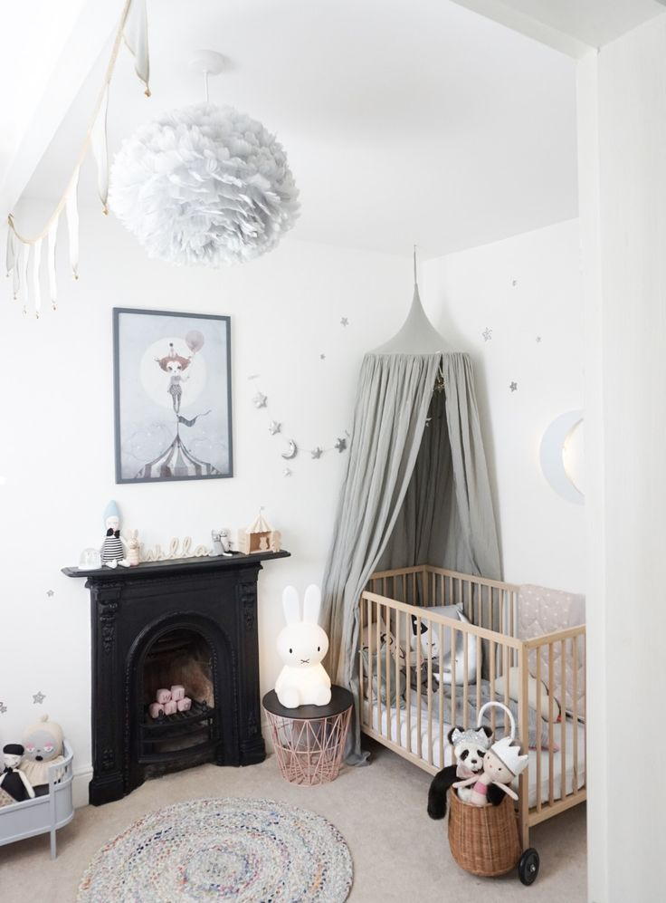 Willa's grey and white nursery with accents of dusty pink. Prints by Mrs Mighetto and Numero74 grey canopy above the cot.  Garland by Velveteen Babies, and Eos Grey feather light fitting. Ferm living pink wire basket as a stand for Miffy light. velveteenbabies.com