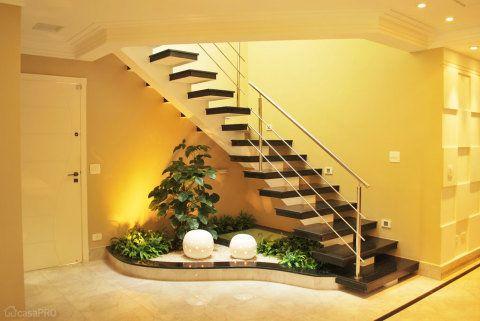 Jardim interno na área abaixo da escada. Proposta de poucos tipos de vegetação: um Filodendro, algumas forrações, pedrisco e elemento ornamental de iluminação. Projeto de Lilia Toti.