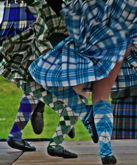 Colourful swirling kilts of Highland dancers at the Highland games in Scotland.