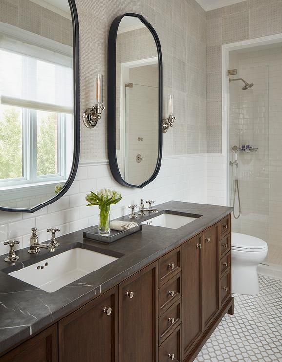Oval Black Vanity Mirrors Hang From A Gray Grid Wallpapered Wall