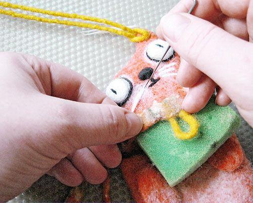 Последние штрихи к портрету кота: прикалываем немного серой шерсти по контуру глаз, затем «обведем» глаза черной шерстью, рисуем зрачки, рот, делаем выпуклый нос и рисуем белые усы. Благодаря валянию при помощи иглы (сухое валяние), для зверей и кукол, выполненных из шерсти, можно не подбирать пластмассовые заготовки глаз и искать их в магазине, а сделать их самим.