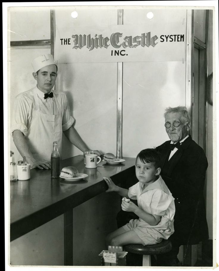 White Castle customer W. Everett (106 years old) is pictured dining at the counter with White Castle customer W. Carson Poe Jr. (4 years old). A White Castle employee is pictured at the counter. Photograph was taken at White Castle number 22. Located at 1709 South 29th St. in Omaha, Nebraska. Photograph was taken by The Omaha World Herald.