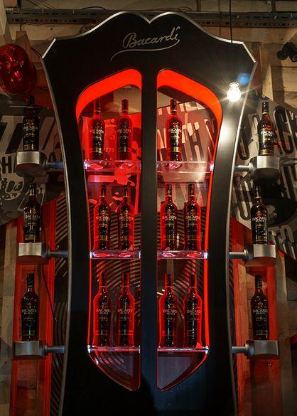 Производство центрального барного шкафа в виде гитарной головки грифа, использование рок атрибутики (кофр, электрогитары), соответствующего стиля оформления (наклейки, плакаты) и подсветки, а так же барных принадлежностей, цветовой гаммы и брендинга Bacardi.