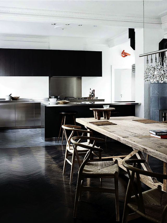 stainless + black cabinetry + rustic wood table + wishbone chairs + herringbone floors
