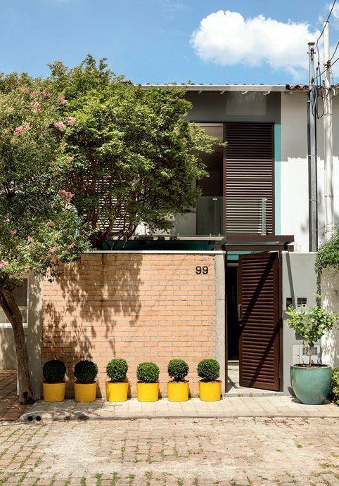 Fachada de casa pequena com muro de tijolo à vista