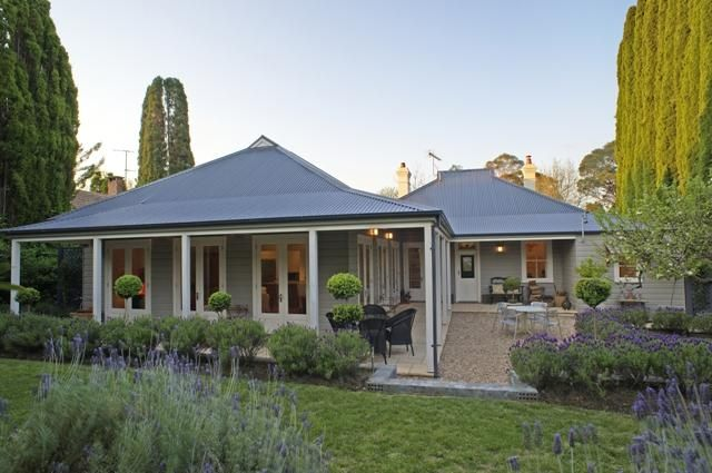 Exterior colours, wrap verandah, gravel pathways, edging and repetitive planting in garden beds.