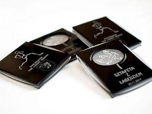 Medal o klasycznym wyglądzie wykonany z materiałów łączonych: czarna i satynowa pleksi.