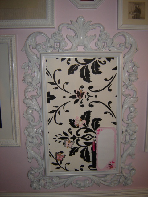 This is a magnet board made using an old picture frame. I just sprayed it white, attached metal sheets to the backing and then wallpapered over the metal sheets with leftover wallpaper.