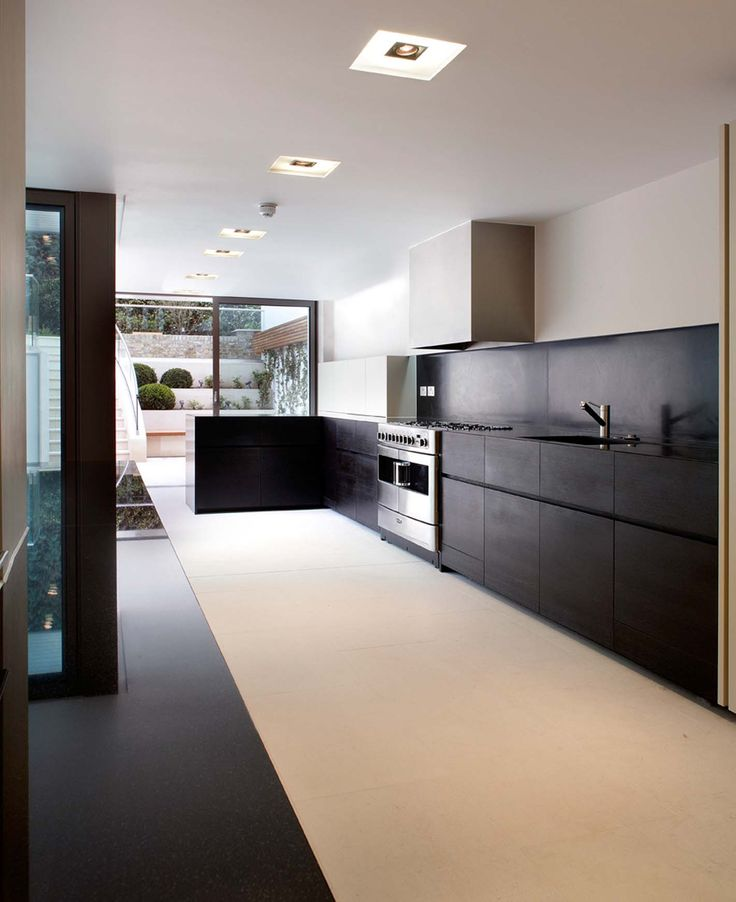 Minotti Gandhara Kitchen, dark oak fronts, Nero Assoluto stone. Excuse the range oven, not my choice, would have been far better with wall mounted ovens to the tall units on the right, and furniture continuing under the hob. image from Spparc Architecture
