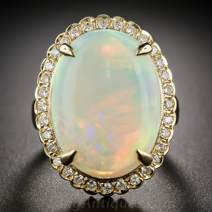 9.77 Carat Opal and Diamond Cluster Ring - 30-1-5635 - Lang Antiques. a multi-hued, rolling refulgent glow that mesmerizes - exactly what an opal should do. The enchanting gemstone, weighing just shy of 10 carats, is surrounded by half-a-carat carat of sparkling round brilliant-cut diamonds and is crafted in gleaming 18 karat yellow gold. Finger size 7. USD 3,850.