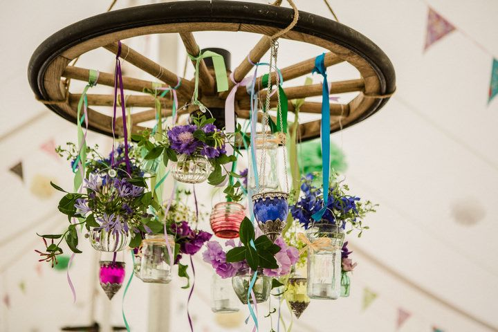 wheel dressed with flowers and jars hanging from marquee roof