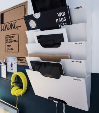 Close-up of a wall newspaper rack used as a customized charging station for tablets