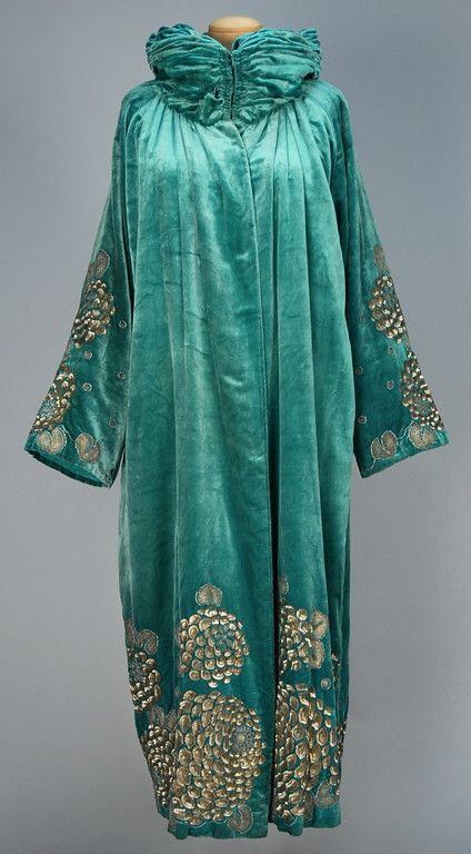 Evening coat, turquoise silk having ruched and padded stand collar, decorated on sleeve and at hem with a stylized floral in platinum sequins and metallic cord embroidery, silk lining, 1923