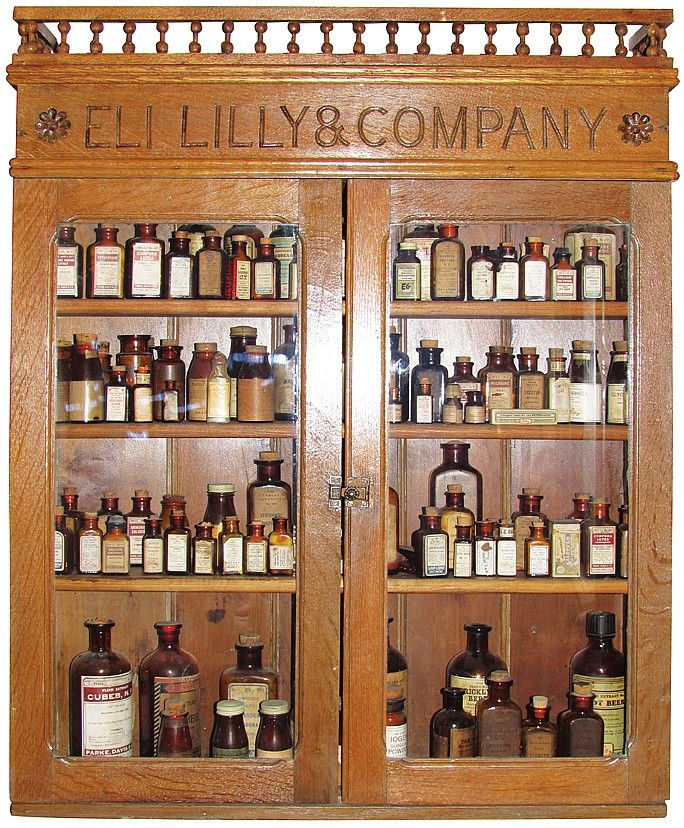 Eli Lilly & Company Oak Store Display Cabinet. Comes with four shelves loaded with pharmacy product.  30 X 38 X 6 1/2 inches.