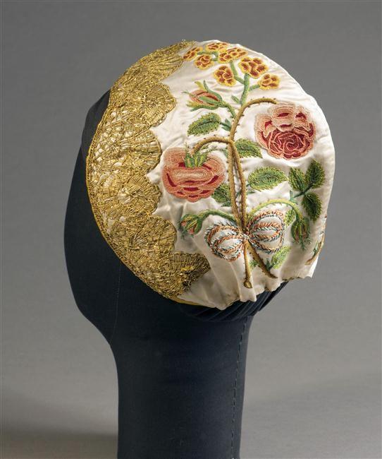 Bonnet à bec à fond en satin de soie ivoire brodé de motifs floraux Anonyme COTE CLICHÉ14-530769N° D'INVENTAIRER.90.33FONDSObjets D'artDESCRIPTION:Coiffe bordée d'une large dentelle métallique dorée et gansée d'un ruban de soie cannelée jaune PÉRIODE 18e siècle 19e siècle période contemporaine de 1789 à 1914 TECHNIQUE/MATIÈRE broderie (technique) , dentelle mécanique , soie (textile)